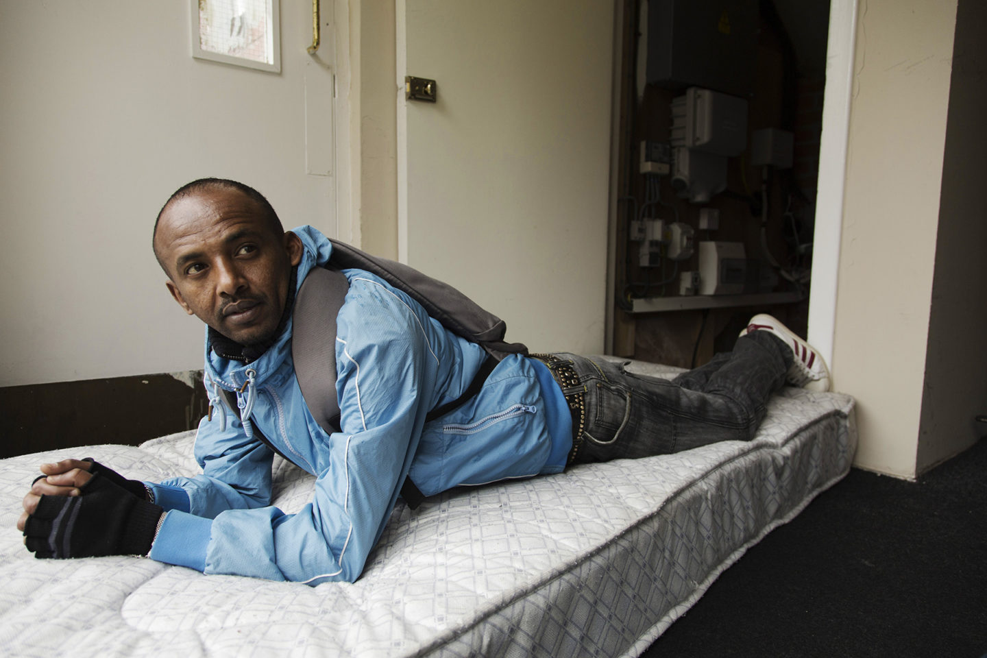 Eritrean refugee on a bed in a Glasgow flat